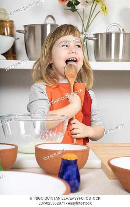 funny three years old child with orange and red apron making and cooking a sponge cake at kitchen home, smiling and licking yogurt in wooden spoon looking side
