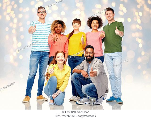 diversity, race, ethnicity and people concept - international group of happy smiling men and women showing thumbs up over holidays lights background