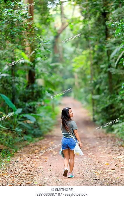 Woman walking and looking back in a jungle path in the Ko Kood island in Thailand