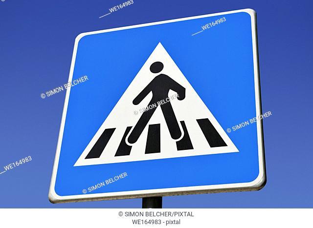 Pedestrian Crossing Sign Against a Blue Sky