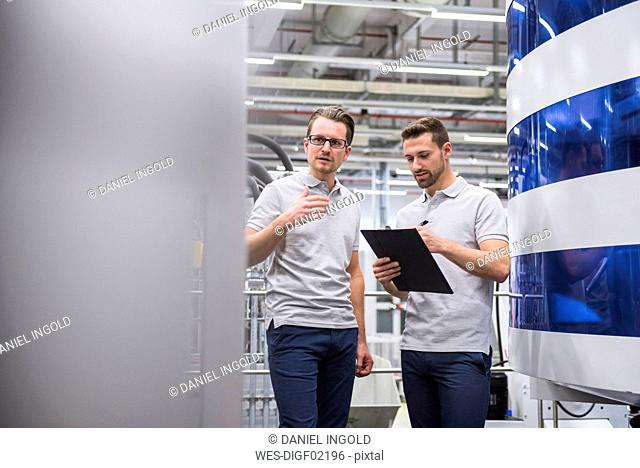 Two men talking at machine in factory shop floor