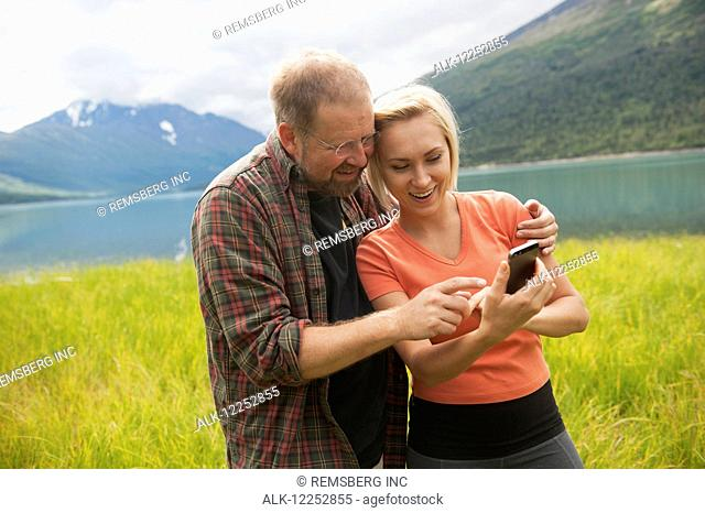 Man and Woman reviewing photos on a smartphone in front of Eklutna Lake, Chugach State Park, Southcentral Alaska