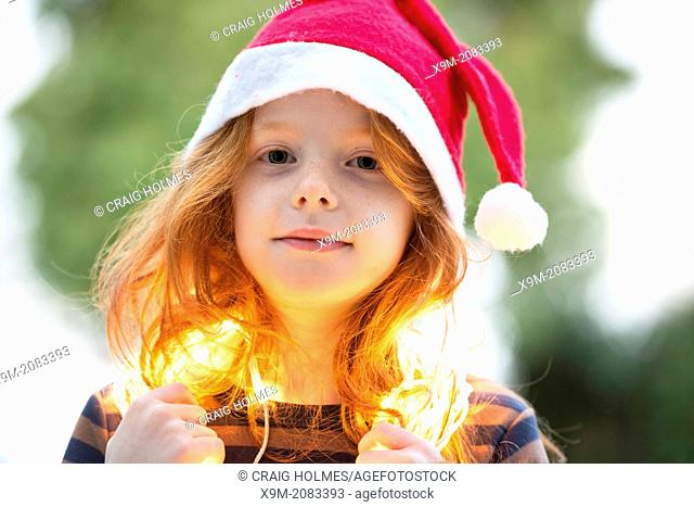 A little girl dressed in a santa hat and fairy Christmas lights