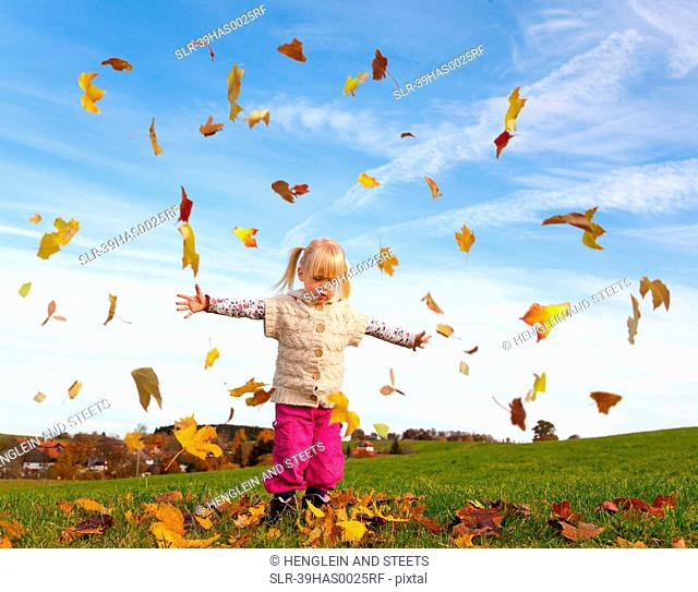 Girl playing in fall leaves