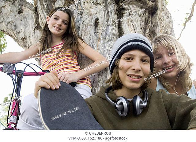 Portrait of a teenage boy with two teenage girls