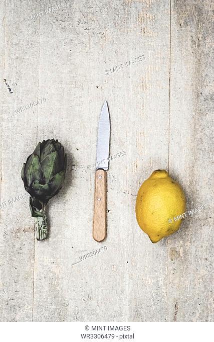 High angle close up of fresh lemon, artichoke and kitchen knife on grey background