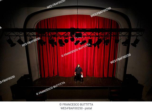 Actor with script standing on theatre stage in front of red curtain