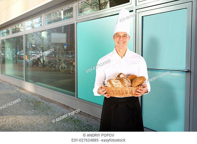 Smiling Baker Wearing White Uniform Holding A Basket Full Of Bread Loaf