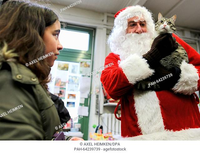 St. Nicholas holds 'Nikolaus' the cat in his arms at the animal shelter on Sueder-Strasse in Hamburg, Germany, 06 December 2015