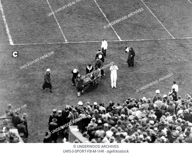 New Haven, Connecticut: October 25, 1930. Yale's Albie Booth is carried off the field on a stretcher after being injured after intercepting a pass from the Army...