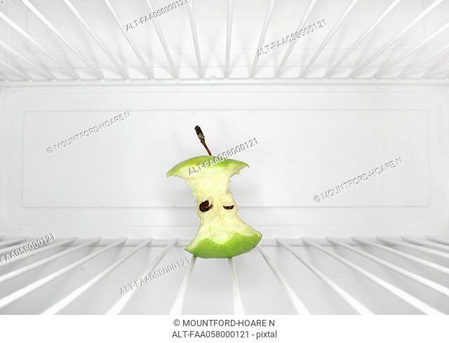 Single apple core sitting on shelf inside refrigerator