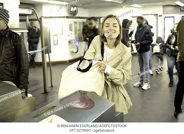 fashionable woman searching for ticket in handbag to enter public transport system, metro, in Paris, France