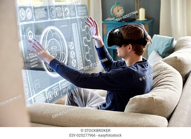 Man Sitting On Sofa At Home Wearing Virtual Reality Headset