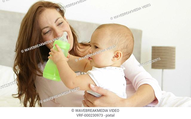 Smiling young mother watching her baby girl drink her bottle at home in bedroom