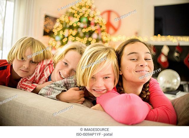 Portrait of teenage girl and brothers on sofa at christmas