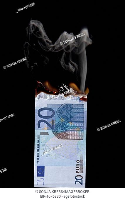 20 euro banknote on fire, in front of black backdrop