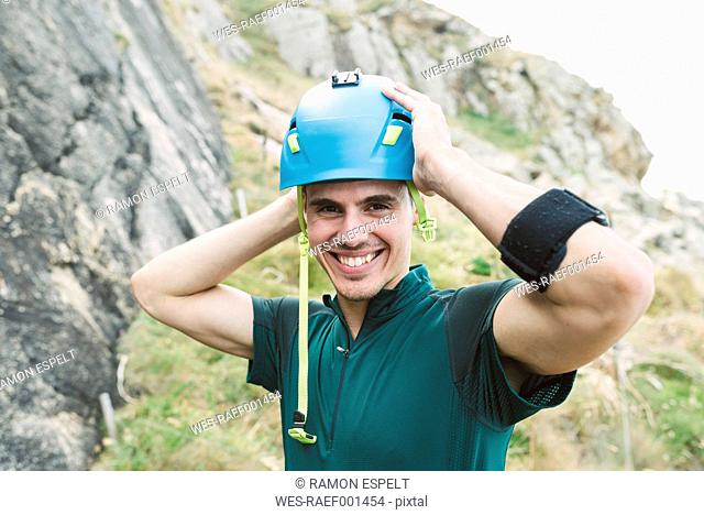 Young man putting on climbing helmet