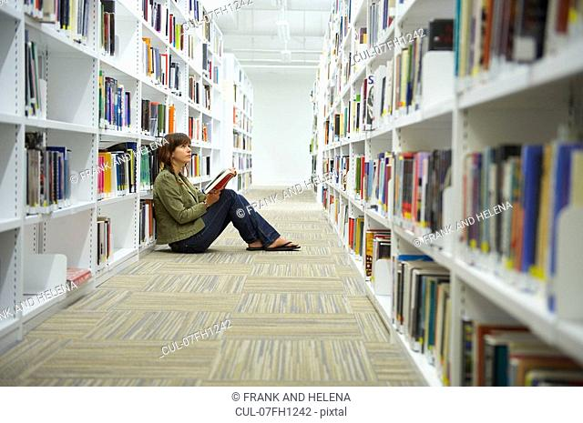 Young woman sitting on library floor