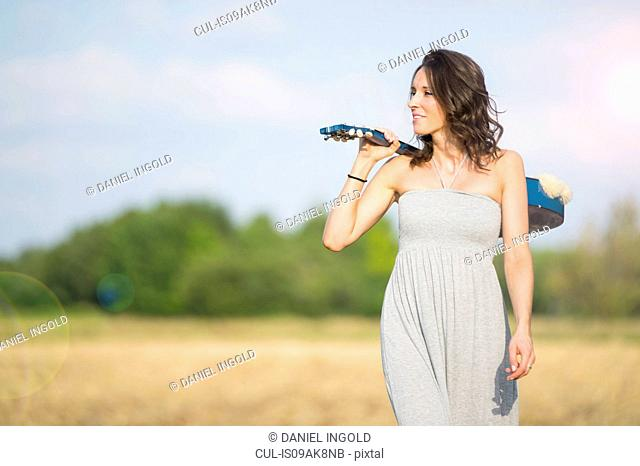 Mid adult woman strolling in field with acoustic guitar over her shoulder