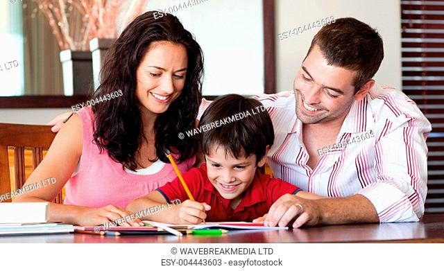 Radiant couple helping his son for homework