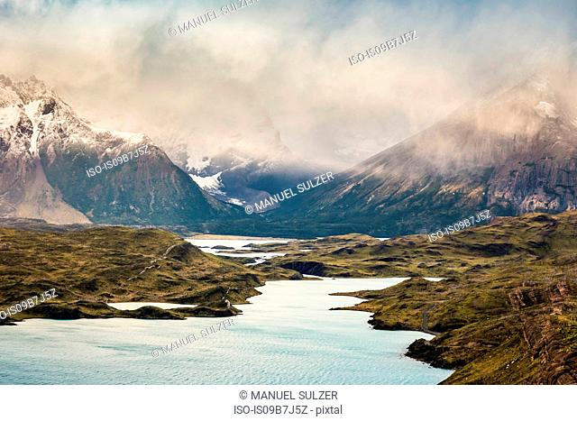 Low cloud and sun rays in river mountain landscape, Torres del Paine National Park, Chile