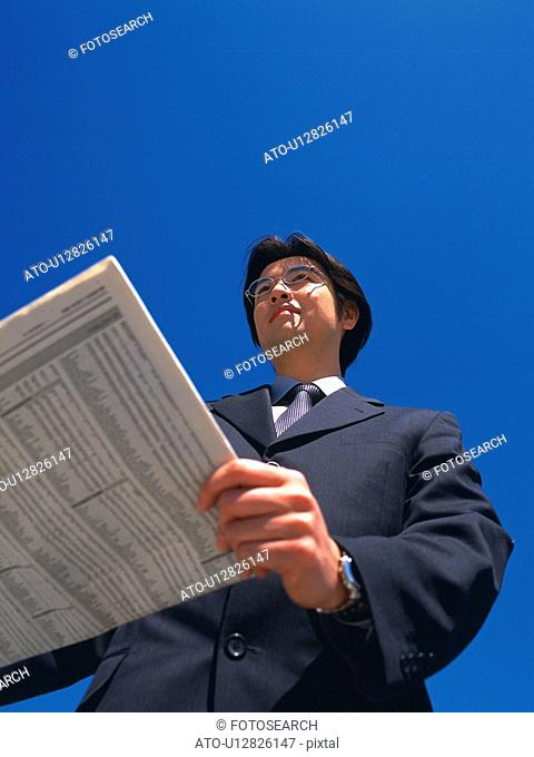 Businessman looking away and holding news paper, Low Angle View