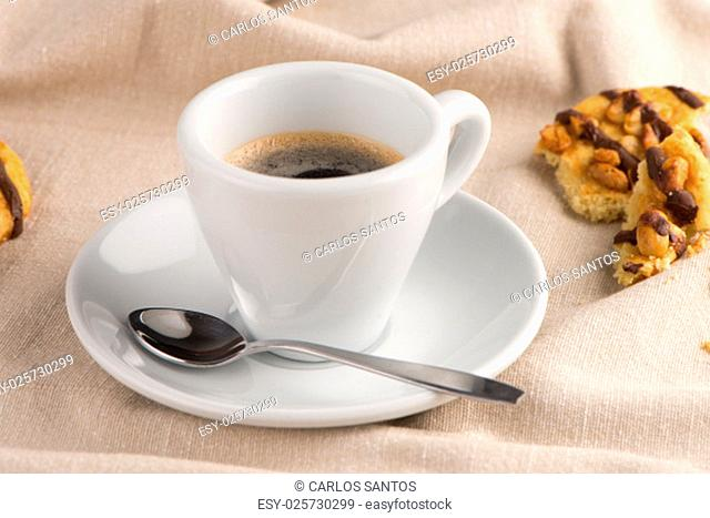 White coffee cup with coffee and around the cup lies some delicious cookies