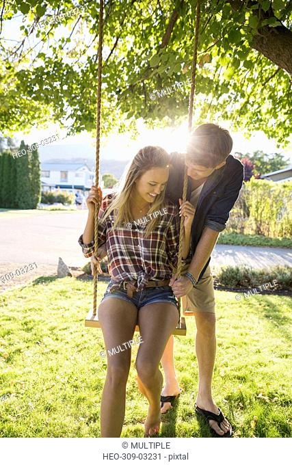 Affectionate young couple swinging at tree swing in sunny summer yard