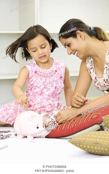 Girl putting a coin into a piggy bank with her mother sitting beside her and smiling