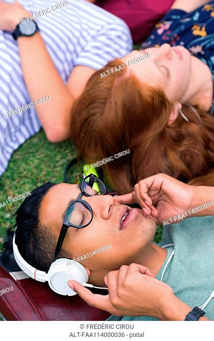 College student lying on grass with friends, listening to headphones