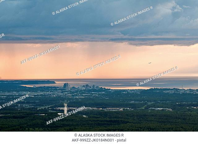 Aerial view of downtown Anchorage in a late summer evening with a rainstorm in the background and a airplane landing at the airport, Southcentral Alaska, Summer