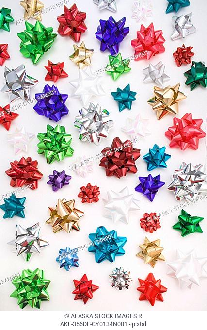 Multiple colorful Christmas gift bows on white background studio portrait