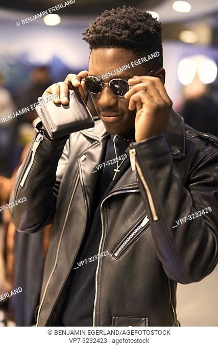 fancy young man with wallet in hands touching sunglasses, African descent, wearing leader jacket, jewellery, Christian cross, in city Munich, Germany