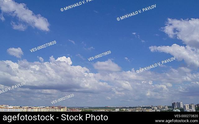 Sunny summer day over the rooftops of the city. The clouds are running fast in the blue sky. Time lapse