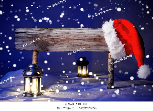 Wooden Christmas Sign And Santa Hat With White Snow In Snowy Scenery. Copy Space Free Text For Advertisement. Blue Silent Night With Snowflakes