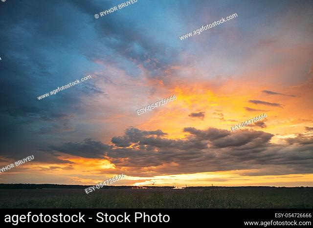 Spring Summer Meadow At Evening Sunset Sunrise. Natural Bright Dramatic Sky In Different Colours Above Countryside Meadow Landscape