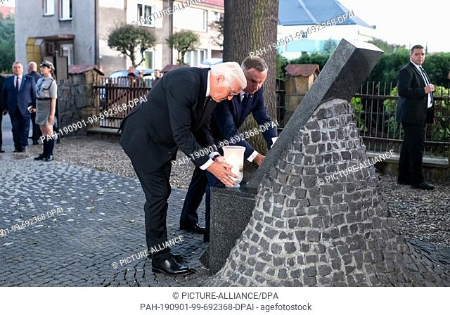 01 September 2019, Poland, Wielun: Federal President Frank-Walter Steinmeier (l) and Polish President Andrzej Duda place candles at the memorial of the...