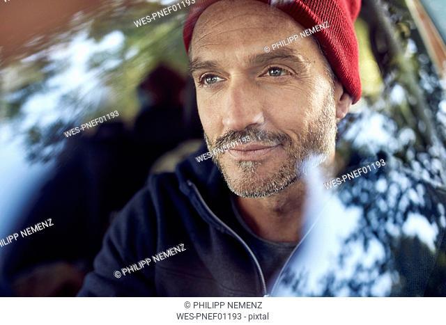Portrait of bearded mature man behind windscreen
