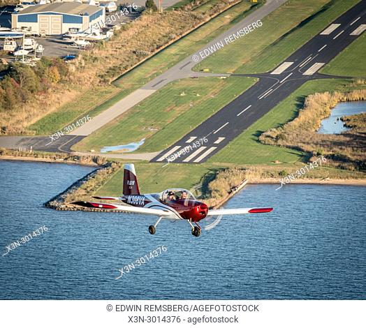 Red Vans RV-12 light sport aircrafts takes off from runway and into the skies on the Chesapeake Bay, Stevensville, Maryland, USA