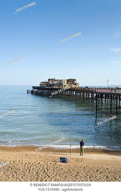 Man fishing on the beach by the pier, Hastings, East Sussex, England, UK