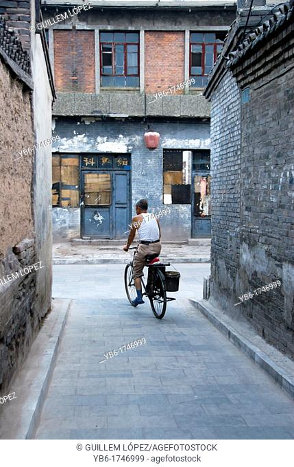 local chinese man on a biking in the streets of Pingyao, Shaanxi Province, China