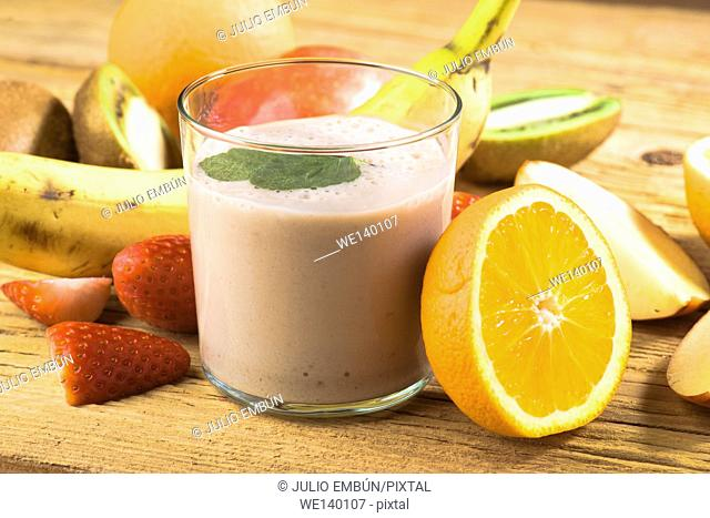 Natural banana smoothie surrounded by fruit on wooden base