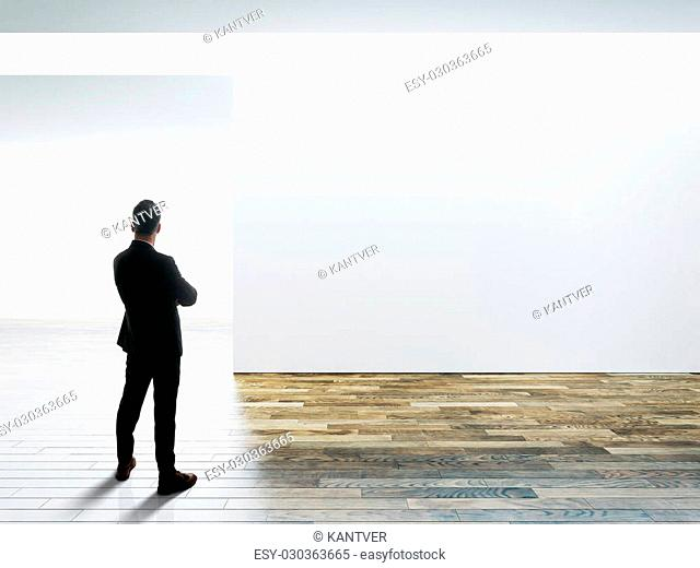 Business man stands opposite big white wall in museum interior with wooden floor. Horizontal