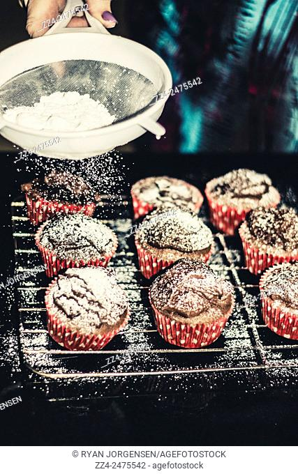Classic home cooking concept of a woman siving up icing sugar on freshly cooked muffins. Icing on the cake