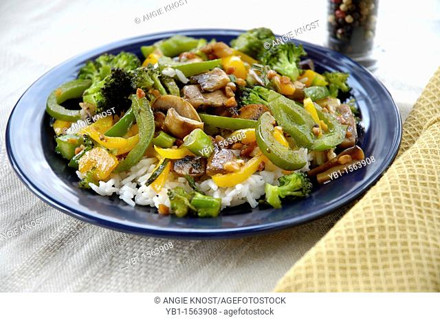 Asian style stir fry including yellow and green peppers, mushrooms and broccoli on a bed of white rice. Can illustrate Asian cookery, wok cooking, vegetarian