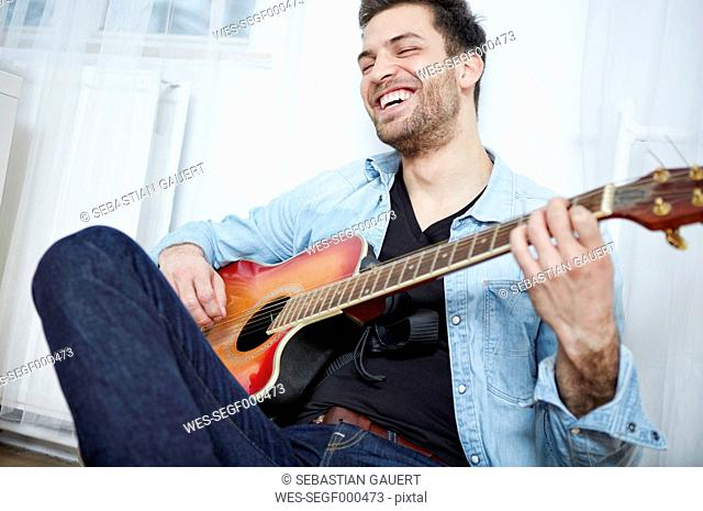 Happy young man playing guitar
