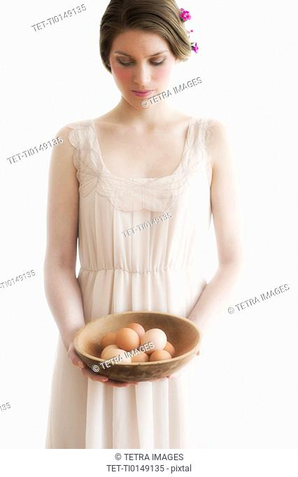 Young woman carrying basket of eggs