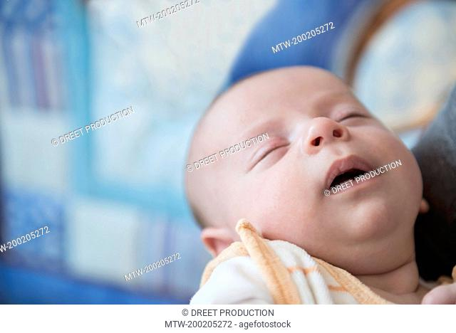 Baby boy sleeping in arms of father, close up