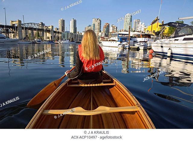 Girl paddling canoe in False Creek off Granville Island, Burrard Bridge and downtown condominiums in background, Vancouver, British Columbia, Canada
