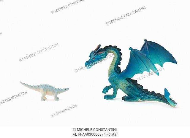 Toy dinosaur and toy dragon, face to face